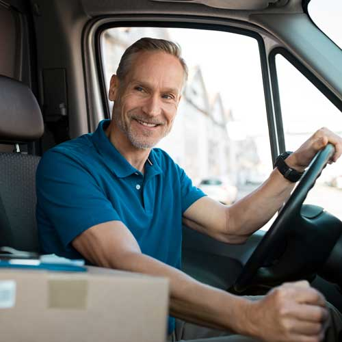 Man in a van smiling with a parcel next to him